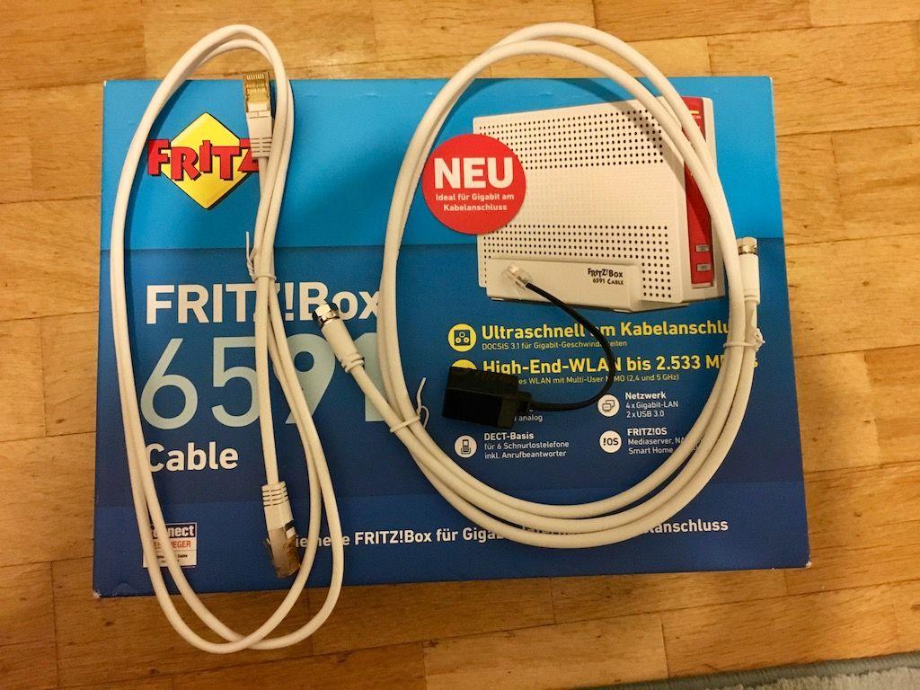 Die Fritz!Box mit Zubehör: Lankabel, Coaxkabel, Analog-Telefonanschluss, Netzteil (nicht im Bild)